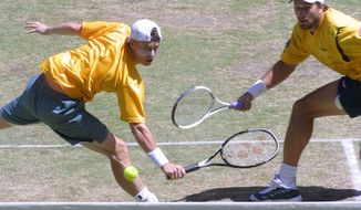 **FILE** Australia's Lleyton Hewitt, left, and Patrick Rafter reach for a shot in the match against France's Cedric Pioline and Fabrice Santoro, both unseen, in the doubles of the Davis Cup Finals in Melbourne, Australia, Saturday, Dec. 1, 2001. Pioline and Santoro won 2-6, 6-3, 7-6, 6-1, taking the French team to a 2-1 lead. (AP Photo/Rob Griffith)