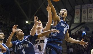 Butler's Erik Fromm (4) battles Georgetown's Mikael Hopkins (3) and Reggie Cameron (1) for a rebound in the first half of an NCAA college basketball game, Saturday, Jan. 11, 2014, in Indianapolis. (AP Photo/Doug McSchooler)