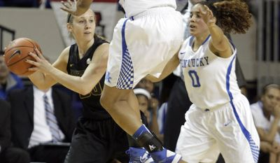 Missouri's Morgan Eye, left, looks for an opening near Kentucky's Bria Goss (13) and Janee Thompson during the first half of an NCAA college basketball game on Sunday, Jan. 12, 2014, in Lexington, Ky. (AP Photo/James Crisp)