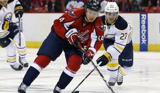 Washington Capitals center Mikhail Grabovski (84), from Germany, looks to pass as he defended by Buffalo Sabres right wing Matt D'Agostini (27) in the first period of an NHL hockey game on Sunday, Jan. 12, 2014, in Washington. (AP Photo/Alex Brandon)
