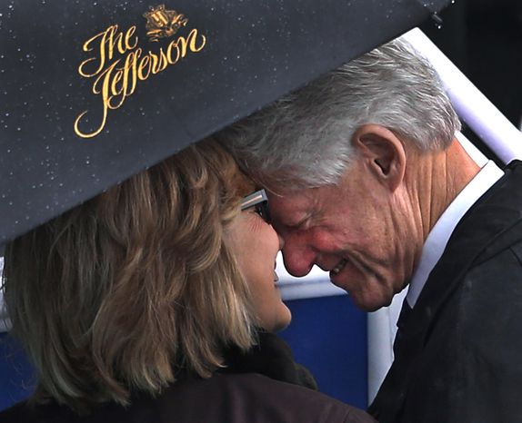 Former President Bill Clinton and his wife, former Secretary of State Hillary Rodham Clinton, share a moment under an umbrella before the rainy inauguration of democratic Virginia Gov. Terry McAuliffe in Richmond, Va., Jan. 11, 2014. The umbrella came from the five-star Jefferson Hotel. (AP Photo/Richmond Times-Dispatch, P. Kevin Morley)