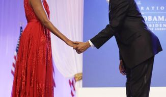 ** FILE ** In this Jan. 21, 2013, file photo, President Barack Obama bows as he and first lady Michelle Obama, wearing a ruby-colored chiffon and velvet Jason Wu gown, gets ready to dance at the Inaugural Ball at the Washington Convention Center during the 57th Presidential Inauguration in Washington. Michelle Obama's fashion is making history again, at least for the next year, as her second inaugural gown will be displayed at the Smithsonian Institution. (AP Photo/Charles Dharapak, File)