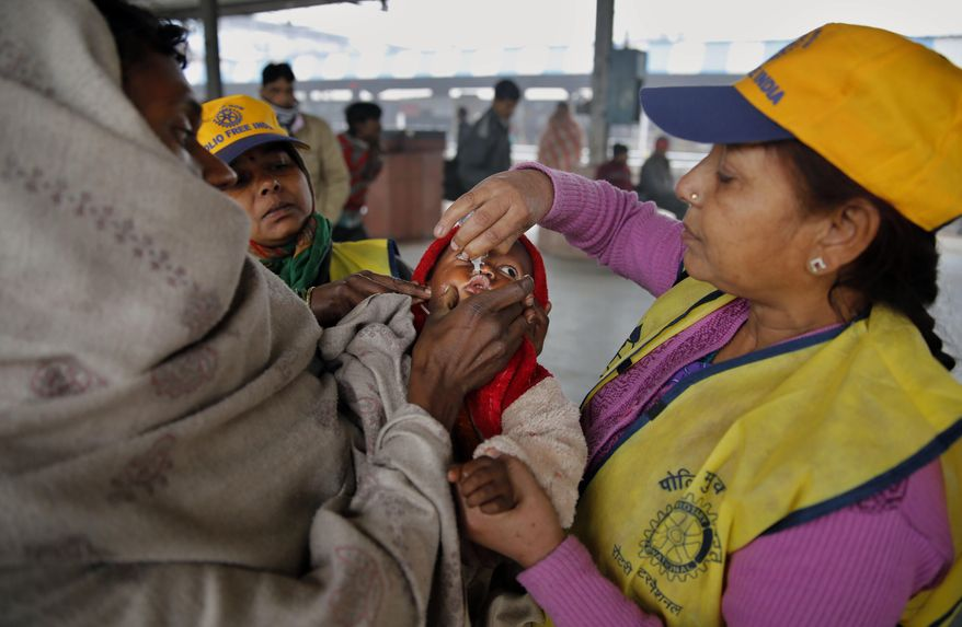 An Indian medical volunteer administers polio immunization drops to a child at a railway station in Allahabad, India, Monday, Jan. 13, 2014. India on Monday marked three years since its last polio case was reported, a major milestone in eradicating the crippling disease. (AP Photo/Rajesh Kumar Singh)