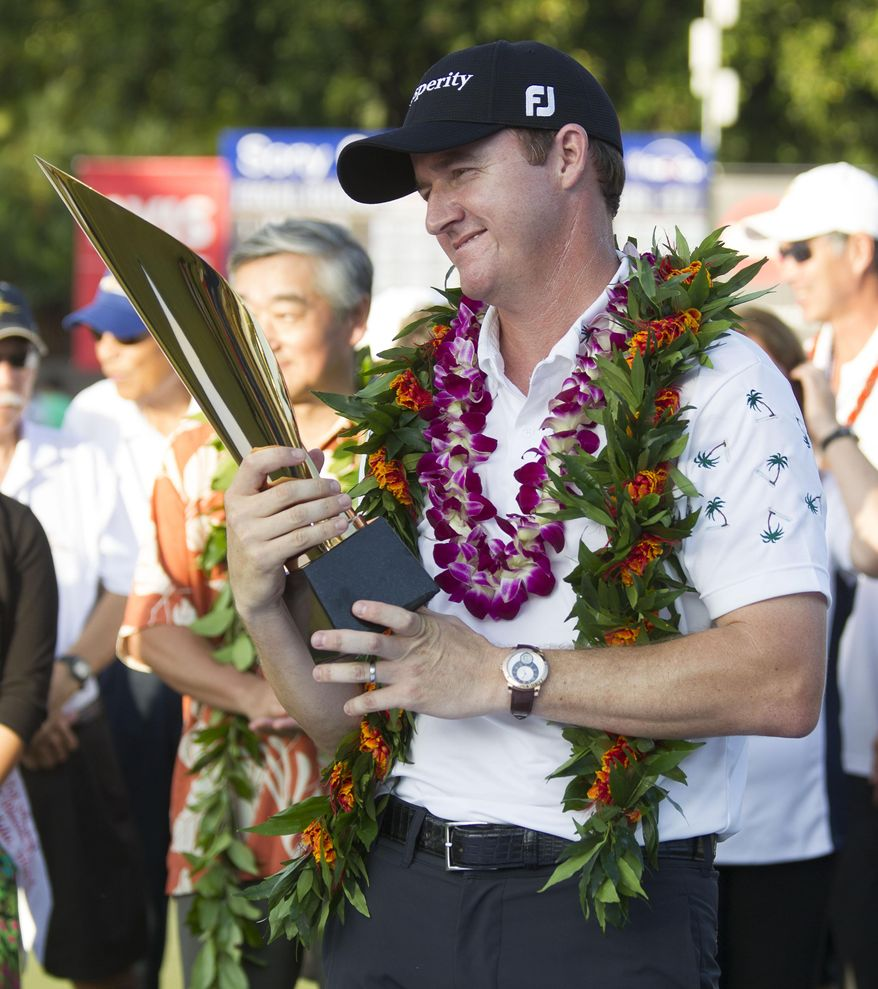 Jimmy Walker looks at the championship trophy after winning the Sony Open golf tournament at Waialae Country Club, Sunday, Jan. 12, 2014, in Honolulu. (AP Photo/Eugene Tanner)