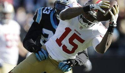 San Francisco 49ers wide receiver Michael Crabtree (15) makes a catch against Carolina Panthers cornerback Melvin White (23) during the first half of a divisional playoff NFL football game, Sunday, Jan. 12, 2014, in Charlotte, N.C. (AP Photo/Gerry Broome)