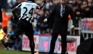 Newcastle United's captain Chieck Tiote, left, celebrates his goal with manager Alan Pardew, right, but the gaol was later disallowed, during their English Premier League soccer match against Manchester City at St James' Park, Newcastle, England, Sunday, Jan. 12, 2014. (AP Photo/Scott Heppell)