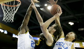 UCLA guard/forward Kyle Anderson, right, blocks a shot by Arizona State center Jordan Bachynski, center, with the help of Tony Parker during the first half of an NCAA college basketball game in Los Angeles, Sunday, Jan. 12, 2014. (AP Photo/Chris Carlson)