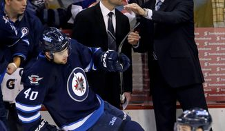 Winnipeg Jets' Assistant Coach Pascal Vincent and head coach Paul Maurice talk during first period NHL hockey action in Winnipeg, Canada, Monday, Jan. 13, 2014. (AP Photo/The Canadian Press, Trevor Hagan)