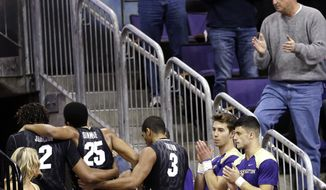 Fans and cheerleaders cheer Colorado's Spencer Dinwiddie (25) as he is assisted from the court after being injured against Washington in the first half of an NCAA college basketball game on Sunday, Jan. 12, 2014, in Seattle. (AP Photo/Elaine Thompson)
