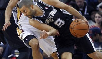 San Antonio Spurs point guard Tony Parker (9) drives around New Orleans Pelicans point guard Brian Roberts in the first half of an NBA basketball game in New Orleans, Monday, Jan. 13, 2014. (AP Photo/Gerald Herbert)