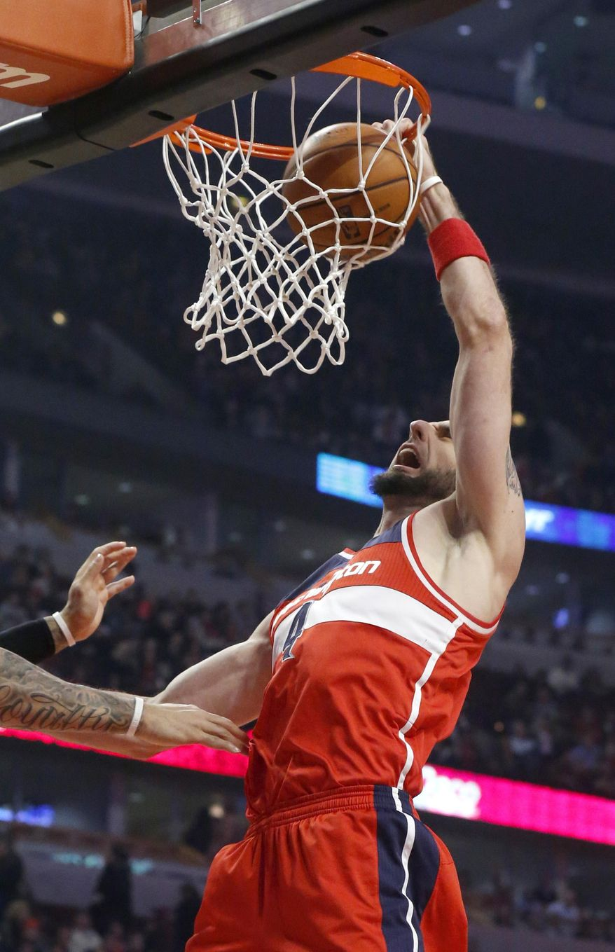Washington Wizards center Marcin Gortat dunks the ball during the first half of an NBA basketball game against the Chicago Bulls, Monday, Jan. 13, 2014, in Chicago. (AP Photo/Charles Rex Arbogast)
