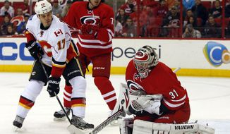 Carolina Hurricanes goalie Anton Khudobin (31) of Kazakhstan, swallows the puck in front of a charging Calgary Flames' Lance Bouma (17) and Hurricanes' Brett Bellemore (73) during the first period of an NHL hockey game in Raleigh, N.C., Monday, Jan. 13, 2014. (AP Photo/Karl B DeBlaker)