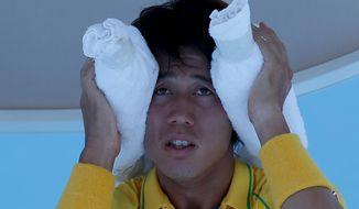 Kei Nishikori of Japan wraps an ice pack around his head during a break in his first round match against Marinko Matosevic of Australia at the Australian Open tennis championship in Melbourne, Australia, Tuesday, Jan. 14, 2014.(AP Photo/Aaron Favila)