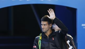 Defending champion Novak Djokovic of Serbia waves as he walks onto Rod Laver Arena to play Lukas Lacko of Slovakia in their first round match at the Australian Open tennis championship in Melbourne, Australia, Monday, Jan. 13, 2014.(AP Photo/Eugene Hoshiko)