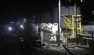 Workers at Freedom Industries continue through the night to empty storage tanks of chemicals into tanker trucks at it's plant in Charleston, Va., Sunday, Jan. 12, 2014.  A chemical spill at the company has deprived 300,000 West Virginians of clean tap water for four days.(AP Photo/Steve Helber)