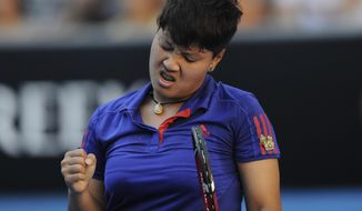 Luksika Kumkhum of Thailand celebrates a point won over Petra Kvitova of the Czech Republic during their first round match at the Australian Open tennis championship in Melbourne, Australia, Monday, Jan. 13, 2014. (AP Photo/Andrew Brownbill)