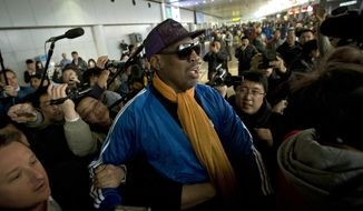 Former NBA basketball player Dennis Rodman is followed by journalists as he arrives at the Capital International Airport in Beijing from Pyongyang, Monday, Jan. 13, 2014. A squad of former basketball stars led by Rodman had a friendly game with North Korean basketball players in Pyongyang. (AP Photo/Alexander F. Yuan)