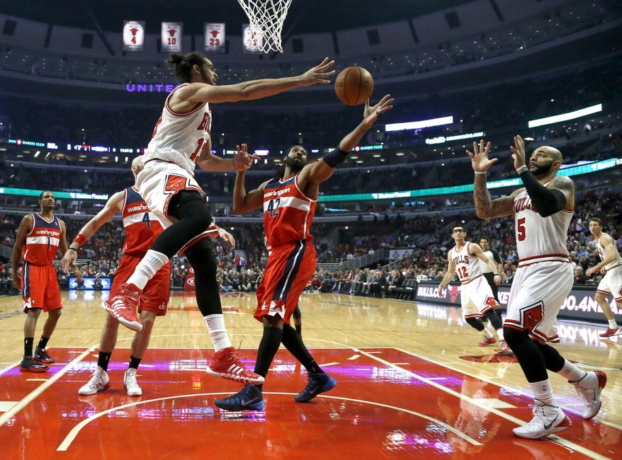 Washington Wizards power forward Nene (42) deflects a pass from Chicago Bulls center Joakim Noah (13) intended for Carlos Boozer (5) during the first half of an NBA basketball game, Monday, Jan. 13, 2014, in Chicago. (AP Photo/Charles Rex Arbogast)