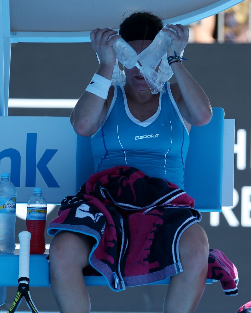 Lourdes Dominguez Lino of Spain wraps an ice pack around her face during a break in her first round match against Caroline Wozniacki of Denmark at the Australian Open tennis championship in Melbourne, Australia, Tuesday, Jan. 14, 2014.(AP Photo/Rick Rycroft)