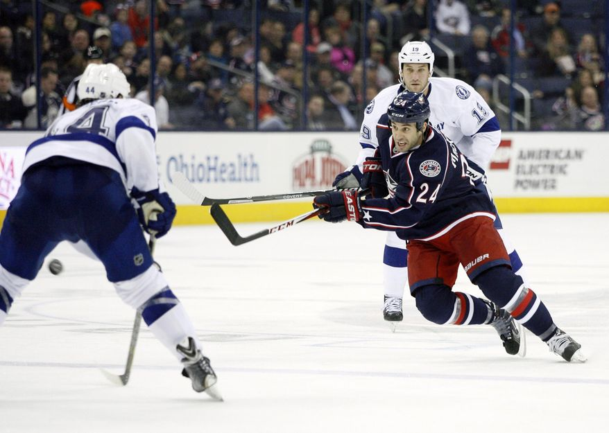 Columbus Blue Jackets' Derek MacKenzie (24) passes to a teammate against the Tampa Bay Lightning during the first period of an NHL hockey game, Monday, Jan. 13, 2014, in Columbus, Ohio. (AP Photo/Mike Munden)