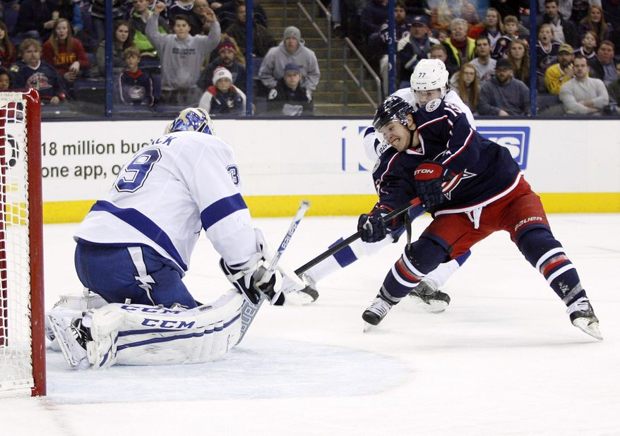 Columbus Blue Jackets' Cam Atkinson (13) shot is blocked by Tampa Bay Lightning goalie Anders Lindback (39), of Sweden, during the second period of an NHL hockey game, Monday, Jan. 13, 2014, in Columbus, Ohio. (AP Photo/Mike Munden)