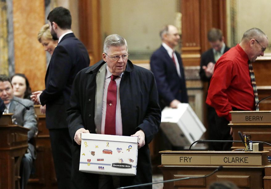 Rep. Dwayne Alons, R-Hull, carries a box to his desk during the opening day of the Iowa Legislature, Monday, Jan. 13, 2014, at the Statehouse in Des Moines, Iowa. (AP Photo/Charlie Neibergall)