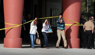Patrons leave Cobb theater after a shooting Monday, Jan. 13, 2014, in Wesley Chapel, Fla. Authorities say a retired Tampa police officer has been charged with fatally shooting a man during an argument over cellphone use at the theater. (AP Photo/The Tampa Tribune, Cliff Mcbride)