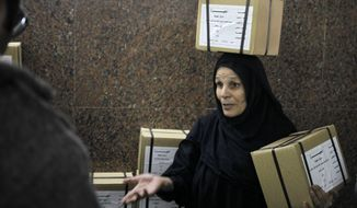 """An Egyptian worker carries boxes of ballots at the Giza courthouse, in Cairo, Egypt, Monday, Jan. 13, 2014. The January 14-15 vote on the draft constitution will be the first real test of the post-Morsi regime. A comfortable """"yes"""" vote and a respectable turnout would be seen as bestowing legitimacy, while undermining the Islamists' argument that Morsi remains the nation's elected president. (AP Photo/Amr Nabil)"""