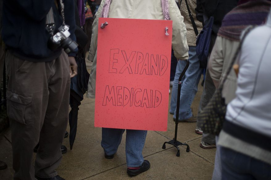 """A demonstrator walks through the crowd with a sign on her back during a protest calling for an expansion to Medicaid outside the State Capitol on the first day of the legislative session, Monday, Jan. 13, 2014, in Atlanta. The protest marking the start of the """"Moral Monday"""" movement in Georgia, aims to put pressure on Gov. Nathan Deal to expand Medicaid under the federal health care law.   (AP Photo/David Goldman)"""