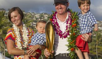 Jimmy Walker, second from right, holds his son Mclain, right, as his wife Erin Walker, left, holds their son Beckett, while they pose for pictures with the Sony Open Trophy after Jimmy won the golf tournament at Waialae Country Club, Sunday, Jan. 12, 2014, in Honolulu. (AP Photo/Eugene Tanner)