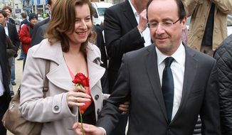 FILE - In this May 5, 2012 file photo, French Socialist Party candidate for the presidential election Francois Hollande, right, offers a rose to his companion Valerie Trierweiler, in Tulle, southwestern France. The woman considered France's first lady was hospitalized after a report the president is having an affair with an actress, her office said Sunday, as a poll was released showing the French shrugging off any liaison as none of their business. (AP Photo/Bob Edme, File)
