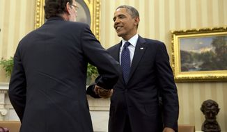 Spanish Prime Minister Mariano Rajoy, left, shakes hands with President Barack Obama after their meeting in the Oval Office of the White House in Washington, Monday, Jan. 13, 2014. (AP Photo/Jacquelyn Martin)