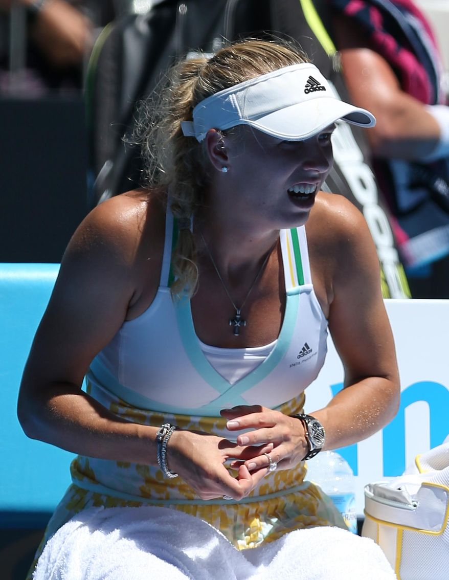 Caroline Wozniacki of Denmark puts her engagement ring on following her win over Lourdes Dominguez Lino of Spain in their first round match at the Australian Open tennis championship in Melbourne, Australia, Tuesday, Jan. 14, 2014. Wozniacki recently announced her engagement to Northern Ireland golfer Rory McIlroy. (AP Photo/Rick Rycroft)