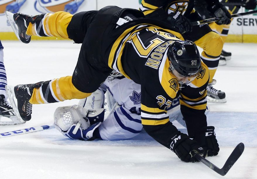 Boston Bruins center Patrice Bergeron (37) falls over Toronto Maple Leafs goalie Jonathan Bernier in the second period of an NHL hockey game in Boston, Tuesday, Jan. 14, 2014. (AP Photo/Elise Amendola)