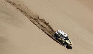 """Mini driver Joan """"Nani"""" Roma of Spain and co-pilot Michel Perin of France race down a dune during the ninth stage of the Dakar Rally between the cities of Calama and Iquique, Chile, Tuesday, Jan. 14, 2014. (AP Photo/Victor R. Caivano)"""