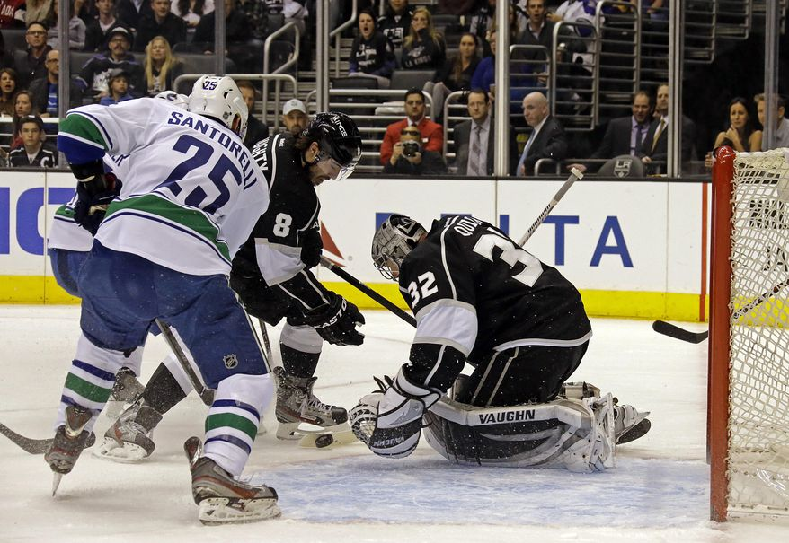 Los Angeles Kings goalie Jonathan Quick (32) deflects the puck with defenseman Drew Doughty (8) as Vancouver Canucks center Mike Santorelli (25) moves in in the first period of an NHL hockey game in Los Angeles, Monday, Jan. 13, 2014. (AP Photo/Reed Saxon)