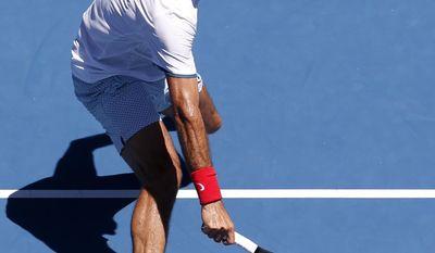 Roger Federer of Switzerland makes a backhand return to James Duckworth of Australia during their first round match at the Australian Open tennis championship in Melbourne, Australia, Tuesday, Jan. 14, 2014.(AP Photo/Eugene Hoshiko)