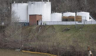 CORRECTS STATE TO W.VA. INSTEAD OF VA. - Workers inspect an area outside a retaining wall around storage tanks where a chemical leaked into the Elk River at Freedom Industries storage facility  in Charleston, W.Va., Monday, Jan. 13, 2014. The ban on tap water for parts of West Virginia was lifted on Monday, ending a crisis for a fraction of the 300,000 people who were told not to drink, wash or cook with water after the chemical spill tainted the water supply. Gov. Earl Tomblin made the announcement at a news conference, five days after people were told to use the water only to flush their toilets. (AP Photo/Steve Helber)