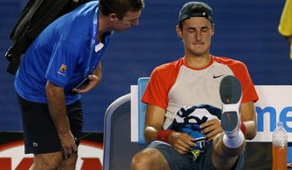 Bernard Tomic of Australia talks to medical staff during his first round match against Rafael Nadal of Spain at the Australian Open tennis championship in Melbourne, Australia, Tuesday, Jan. 14, 2014.(AP Photo/Rick Rycroft)