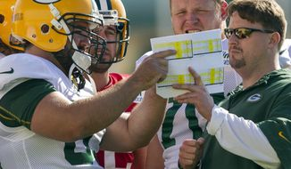 FILE - in this July 28, 2012, file photo, Green Bay Packers quarterbacks coach Ben McAdoo, right, center Jeff Saturday (63), quarterback Aaron Rodgers (12) and offensive guard T.J. Lang (70) talk during NFL football training camp in Green Bay, Wis. The New York Giants on Tuesday, Jan. 14, 2014, hired McAdoo as their new offensive coordinator. (AP Photo/Mike Roemer, File)