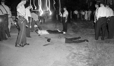 FILE - In this Sept. 24, 1957 file photo, Clarence R. Sanders, an airman at Little Rock Air Force Base, in white jacket, and Ernest Patrick of Little Rock lie on the ground after a chase by police in downtown Little Rock, Ark. The men and their three female companions fled from police after a fight with some white youths.  They were captured after their car went out of control in East Little Rock.  Neither man was seriously hurt were taken police custody. Five decades and $1 billion after an infamous racial episode made Little Rock a symbol of school segregation, the legal fight to ensure all of its children receive equal access to education has ended. (AP Photo/Ferd Kaufman, File)