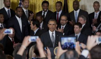 People in the audience take photos and video as President Barack Obama arrives to honor the 2013 NBA Champion basketball team Miami Heat on their second-straight title during a ceremony in the East Room of the White House, Tuesday, Jan. 14, 2014, in Washington. Coach Erik Spoelstra is next to the president, Lebron James is at left. (AP Photo/Carolyn Kaster)