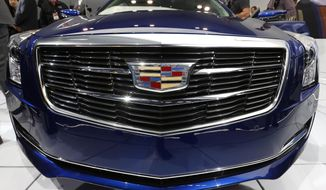 The new Cadillac logo is shown on the 2015 ATS coupe during its debut at media previews during the North American International Auto Show in Detroit, Tuesday, Jan. 14, 2014. (AP Photo/Paul Sancya)