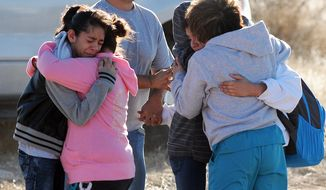 Students are reunited with family following a shooting at Berrendo Middle School, Tuesday, Jan. 14, 2014, in Roswell, N.M. Roswell police said the suspected shooter was arrested at the school, but authorities have not said if there were any injuries. The school has been placed on lockdown. No other details are yet available. (AP Photo/Roswell Daily Record, Mark Wilson)