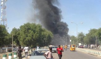In this photo taken with a mobile phone, people runs as smokes billows through the sky after a car bomb explosion at a military post in  Maiduguri, Nigeria, Tuesday, Jan. 14, 2014. A vehicle exploded at a military post in a commercial area in a northeastern Nigerian city on Tuesday, killing at least 17 people and causing pandemonium with blood-spattered bystanders running away and vehicles colliding as drivers rushed to flee.. (AP Photo/Abdulkareem Haruna)