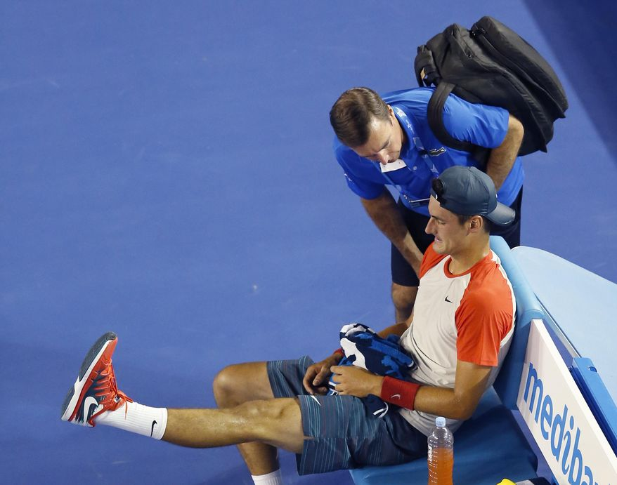 Bernard Tomic of Australia talks to medical staff during his first round match against Rafael Nadal of Spain at the Australian Open tennis championship in Melbourne, Australia, Tuesday, Jan. 14, 2014.(AP Photo/Eugene Hoshiko)