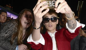 "**FILE** In this Dec. 18, 2013 file photo, singer Justin Bieber takes a ""selfie"" with a fan at a premiere in Los Angeles. (Associated Press/Dan Steinberg, Invision)"