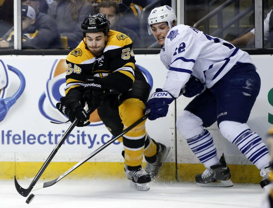 Boston Bruins defenseman Adam McQuaid (54) and Toronto Maple Leafs left wing Mason Raymond, righ, reach to control the puck in the first period of an NHL hockey game in Boston, Tuesday, Jan. 14, 2014. (AP Photo/Elise Amendola)