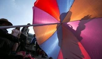 A Thai anti-government protester is silhouetted on an umbrella during a rally at the Victory Monument Tuesday, Jan. 14, 2014 in Bangkok, Thailand. Thailand's political crisis ground on Tuesday as the country's prime minister reiterated her refusal to quit as protesters trying to topple her administration blocked key roads in the heart of Bangkok for a second day. (AP Photo/Wason Wanichakorn)
