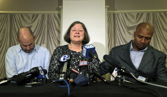 FILE - In this April 9, 2013, file photo, former NFL player Dorsey Levens, right, extends a hand as Mary Ann Easterling, the widow of former NFL player Ray Easterling, reacts as former NFL player Kevin Turner, left, looks on during a news conference in Philadelphia, after a hearing to determine whether the NFL faces years of litigation over concussion-related brain injuries. Judge Anita Brody has announced on Thursday, Aug. 29, 2013, that the NFL and more than 4,500 former players want to settle concussion-related lawsuits for $765 million. (AP Photo/Matt Rourke, File)